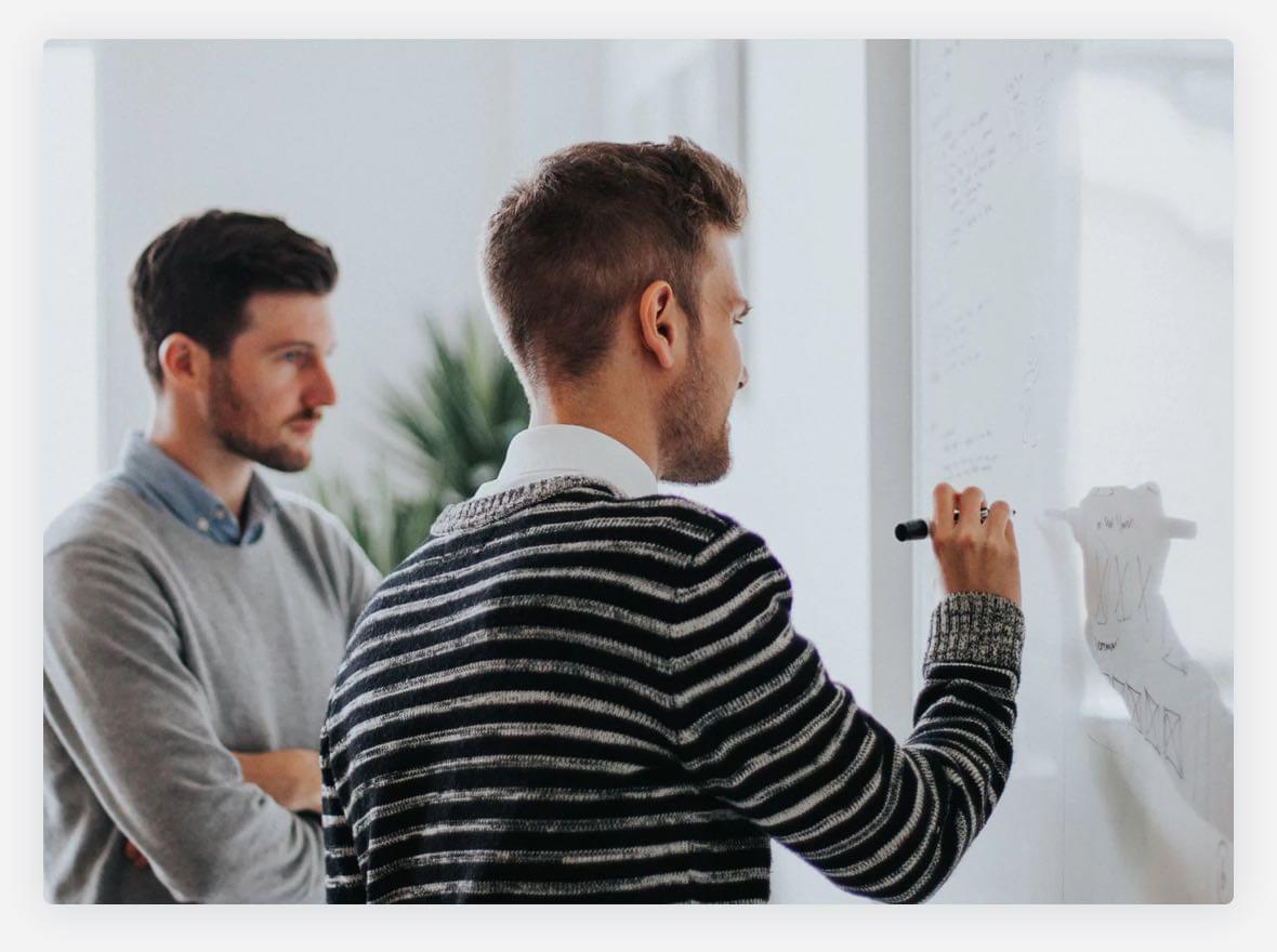 Kaksi miestä suunnittelemassa valkotaulun avulla
